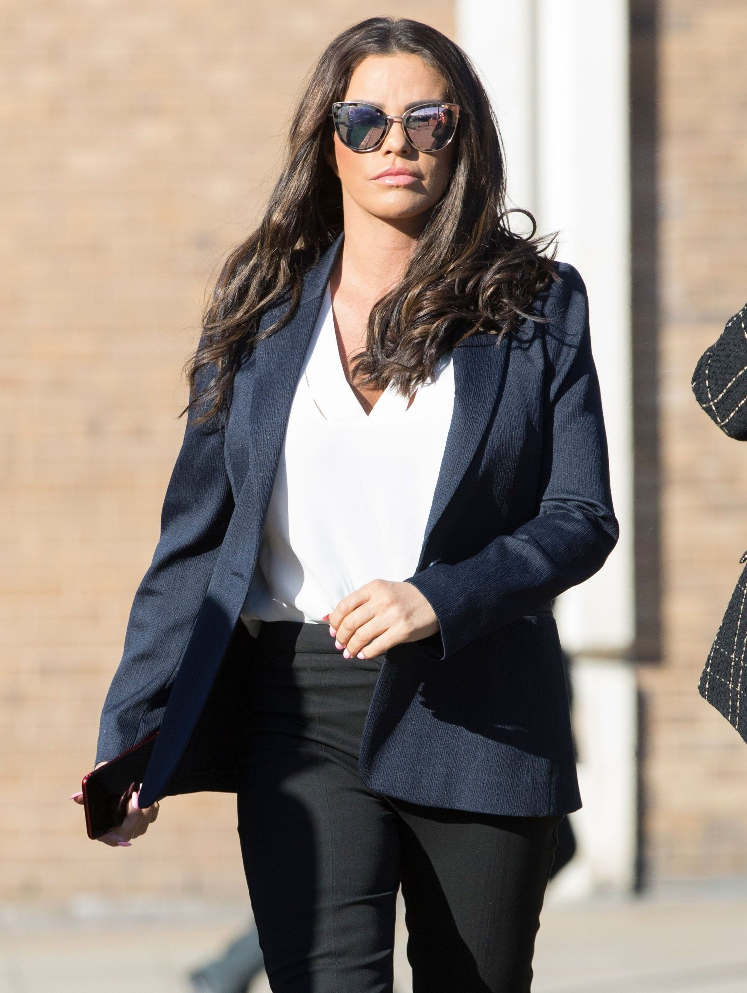 Bilde av Katie Price gående i svart dressjakke, hvit bluse og solbriller