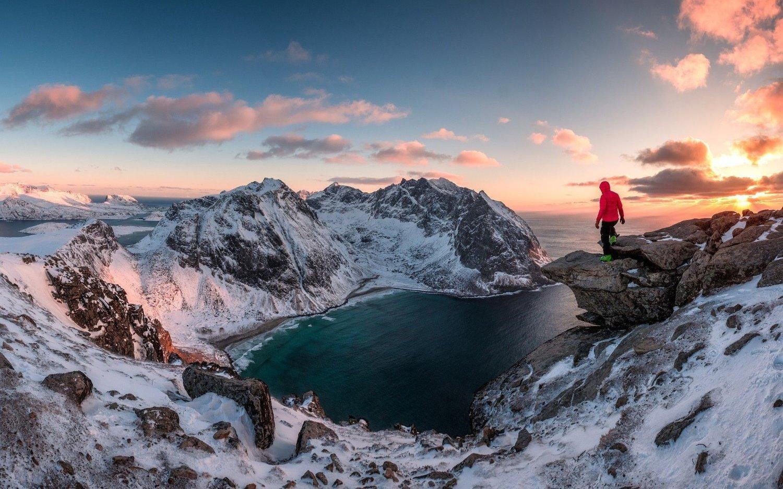 Mann står ute på spissen av et fjell og ser utover en fjord. Ryten fjell