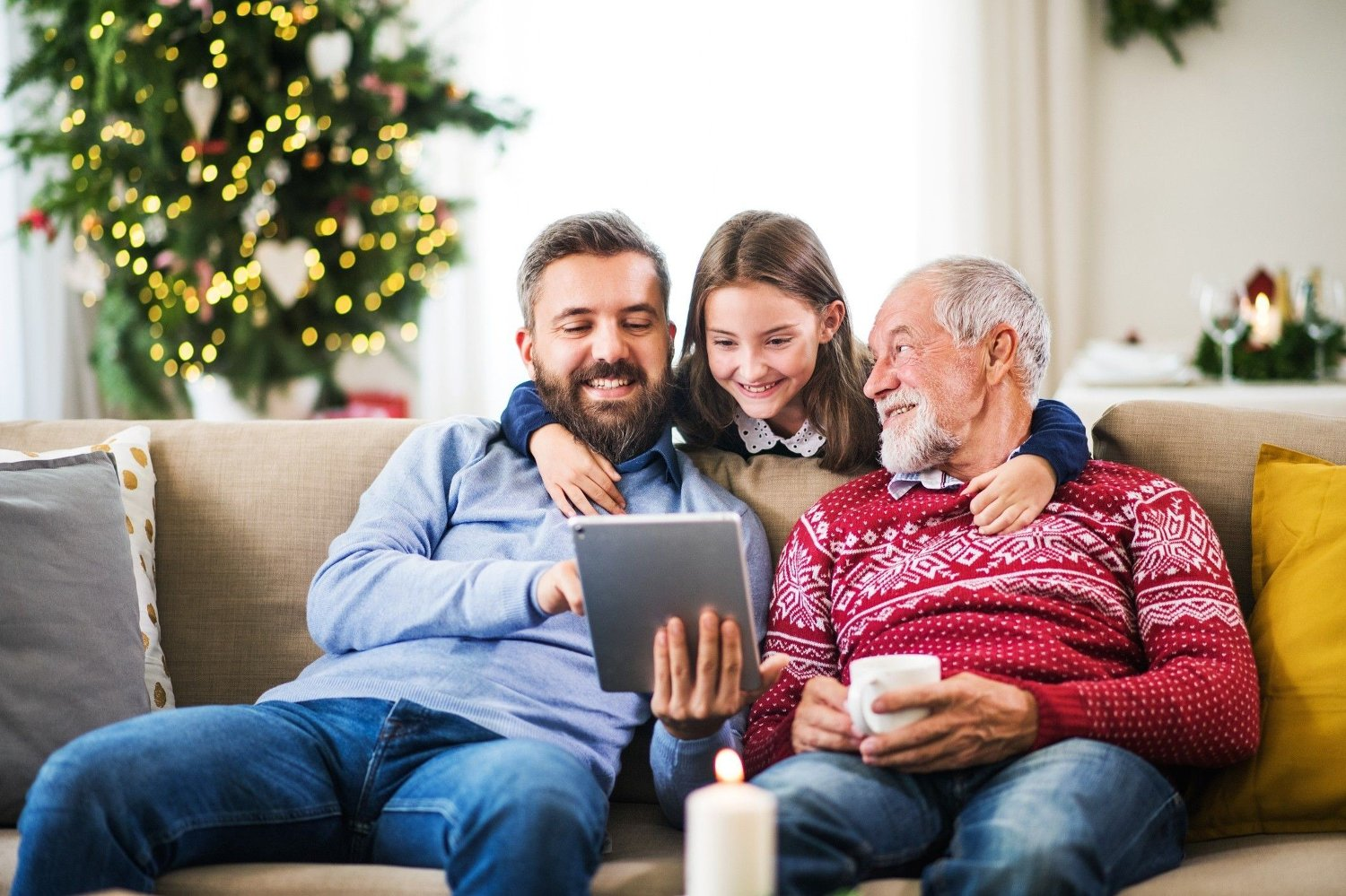 Small girl and her father and grandfather sitting on a sofa at Christmas, using tablet. A happy small girl and her father and grandfather sitting on a sofa at Christmas time, using tablet.