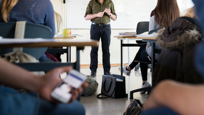 OSLO 20141030. Tenåringer. Lærer og elever i klasserom. Undervisning pågår. Konsentrert. Lærer underviser. Elev med mobiltelefon. NB! MODELLKLARERT