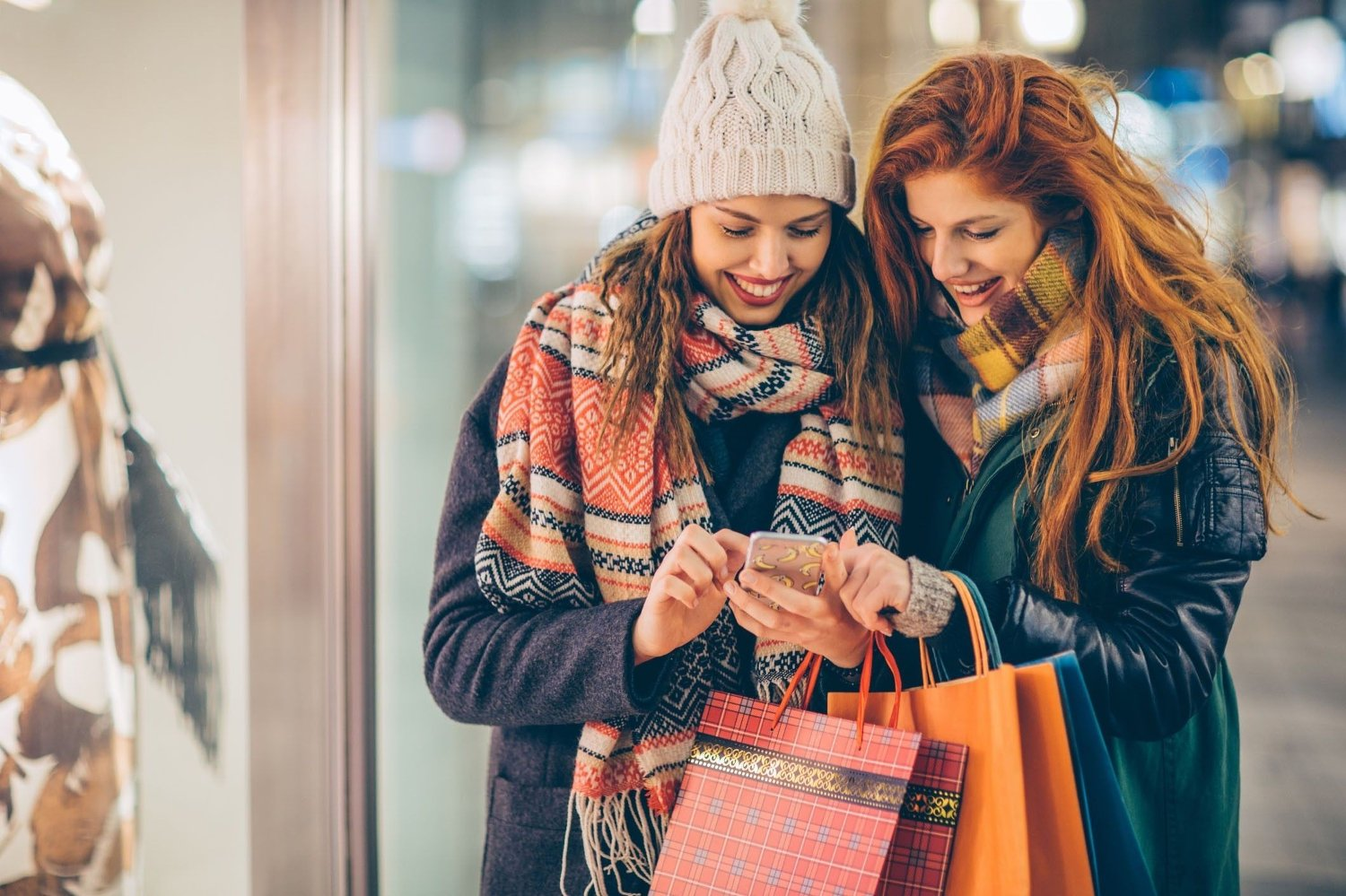 Ready to tackle the next sale Friends walking on city street by night. Checking smart phone to see which shops thay pick. Holding shopping bags. Wearing warm clothing.