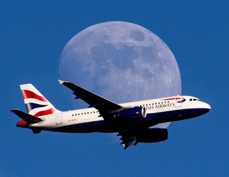 British Airways-fly i luften med jordkloden illustrert i bakgrunnen.