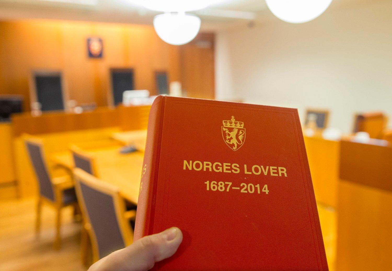 Illustrasjonsfoto: Rettslokale med boken Norge lover i forgrunnen.