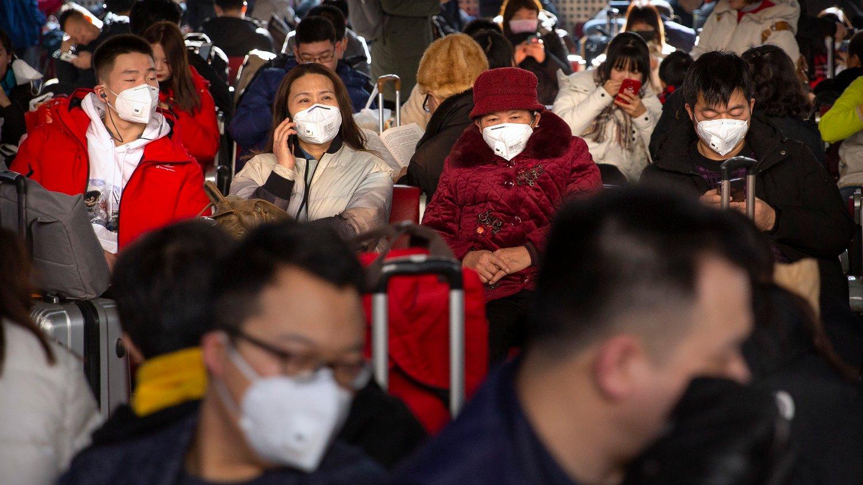 FRYKT: Reisende på Beijings togstasjon har på seg munnbind i frykt for det nye viruset som sprer seg i Kina.