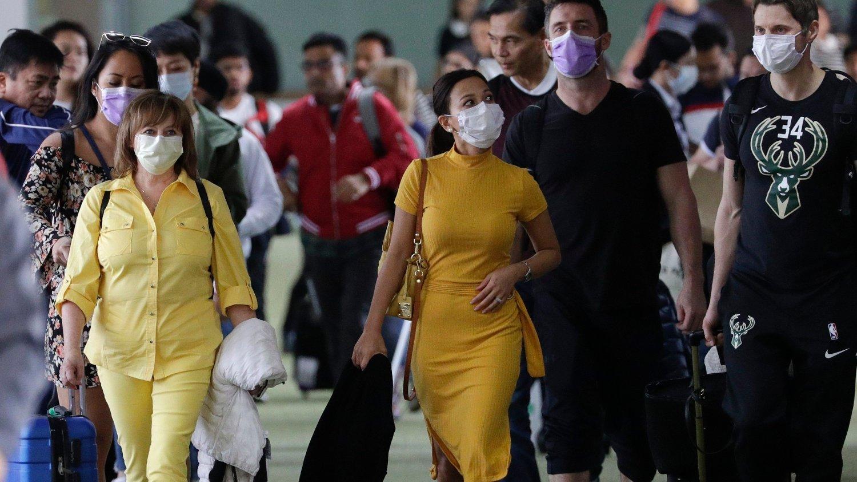 Flypassasjerer iført munnbind på den internasjonale flyplassen i Manila på Filippinene.