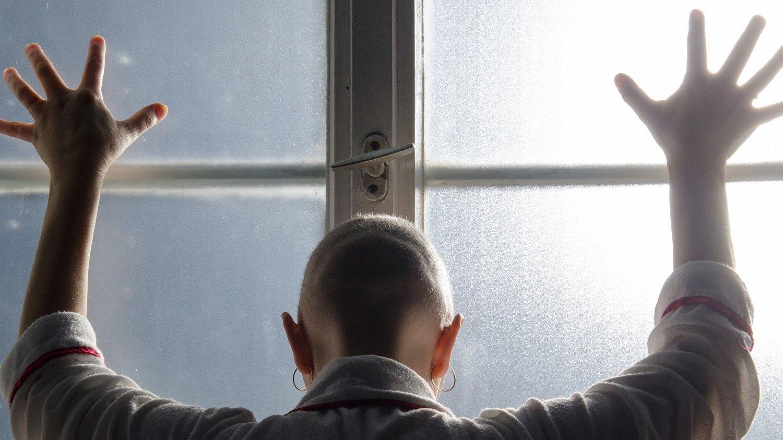 Desperat kvinne bak lukket vindu.