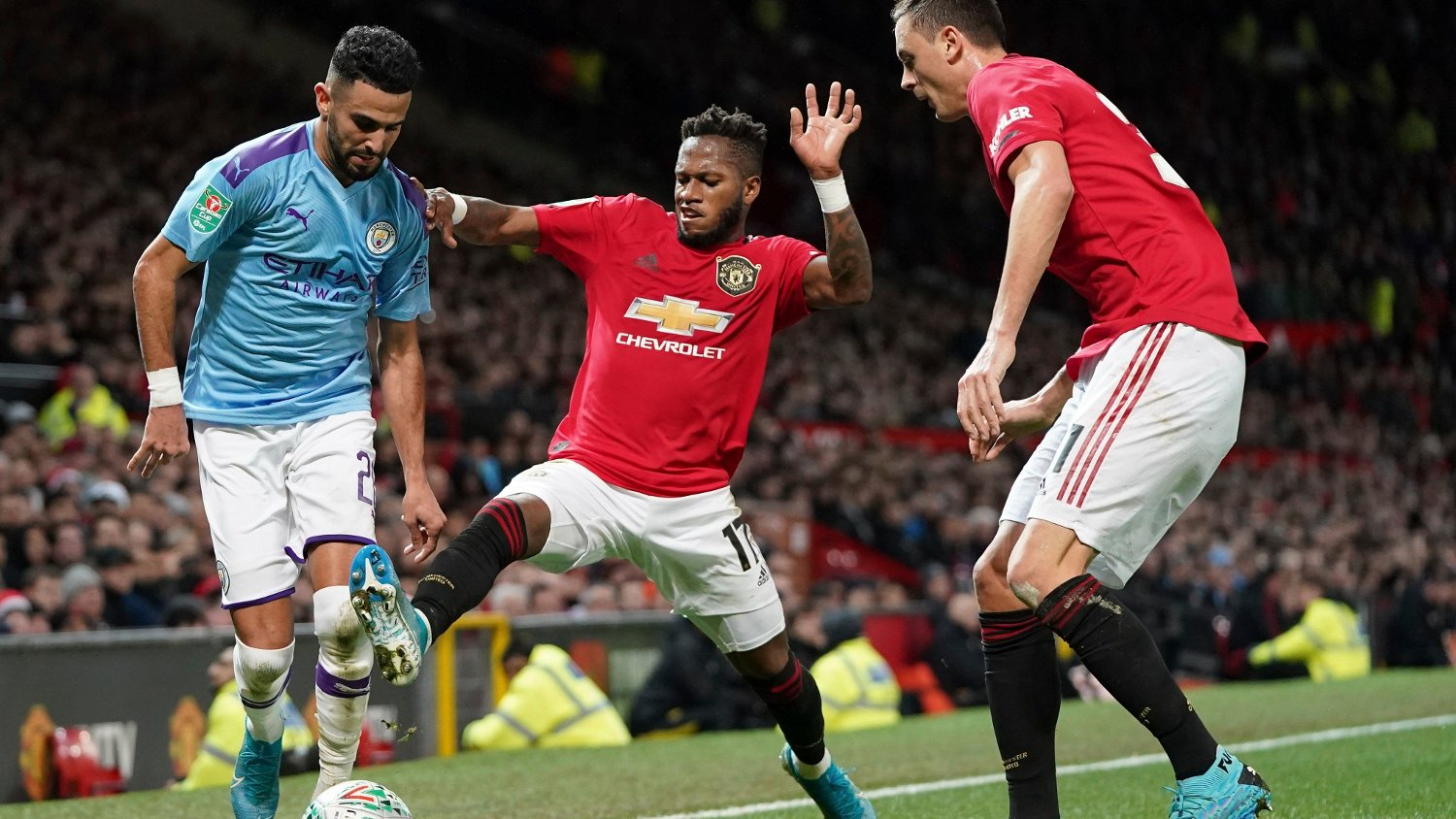 Manchester United's Fred, centre tackles Manchester City's Riyad Mahrez, left, for the ball during the English League Cup semifinal first leg soccer match between Manchester United and Manchester City and at Old Trafford, Manchester, England, Tuesday, Jan. 7, 2020.