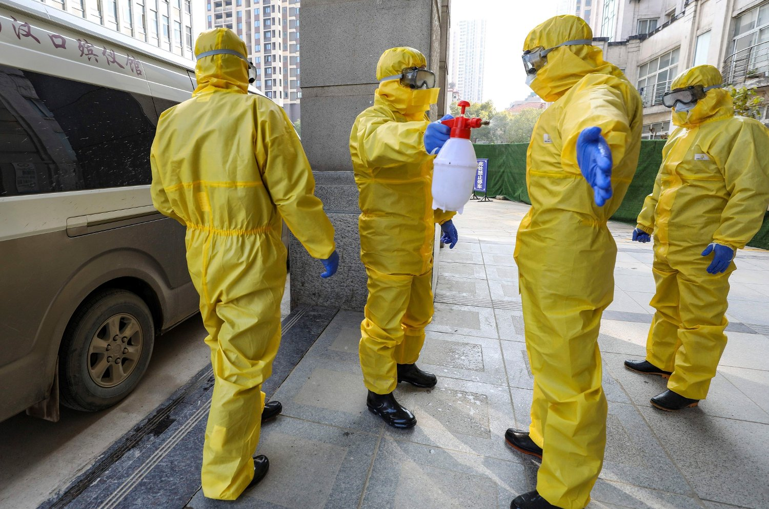 Funeral workers disinfect themselves after handling a virus victim in Wuhan in central China's Hubei Province, Thursday, Jan. 30, 2020. As global anxiety about a new virus rises, Chinese authorities are striving to keep 50 million people in cities at the center of the outbreak both isolated and fed in the biggest anti-disease effort ever attempted.