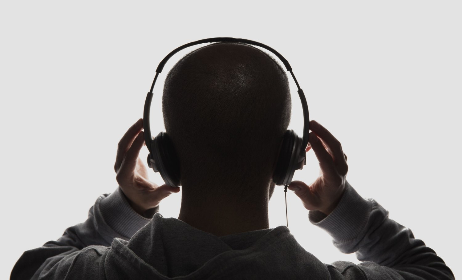 Male silhouette with hands holding headphones Male silhouette with headphones on white background.