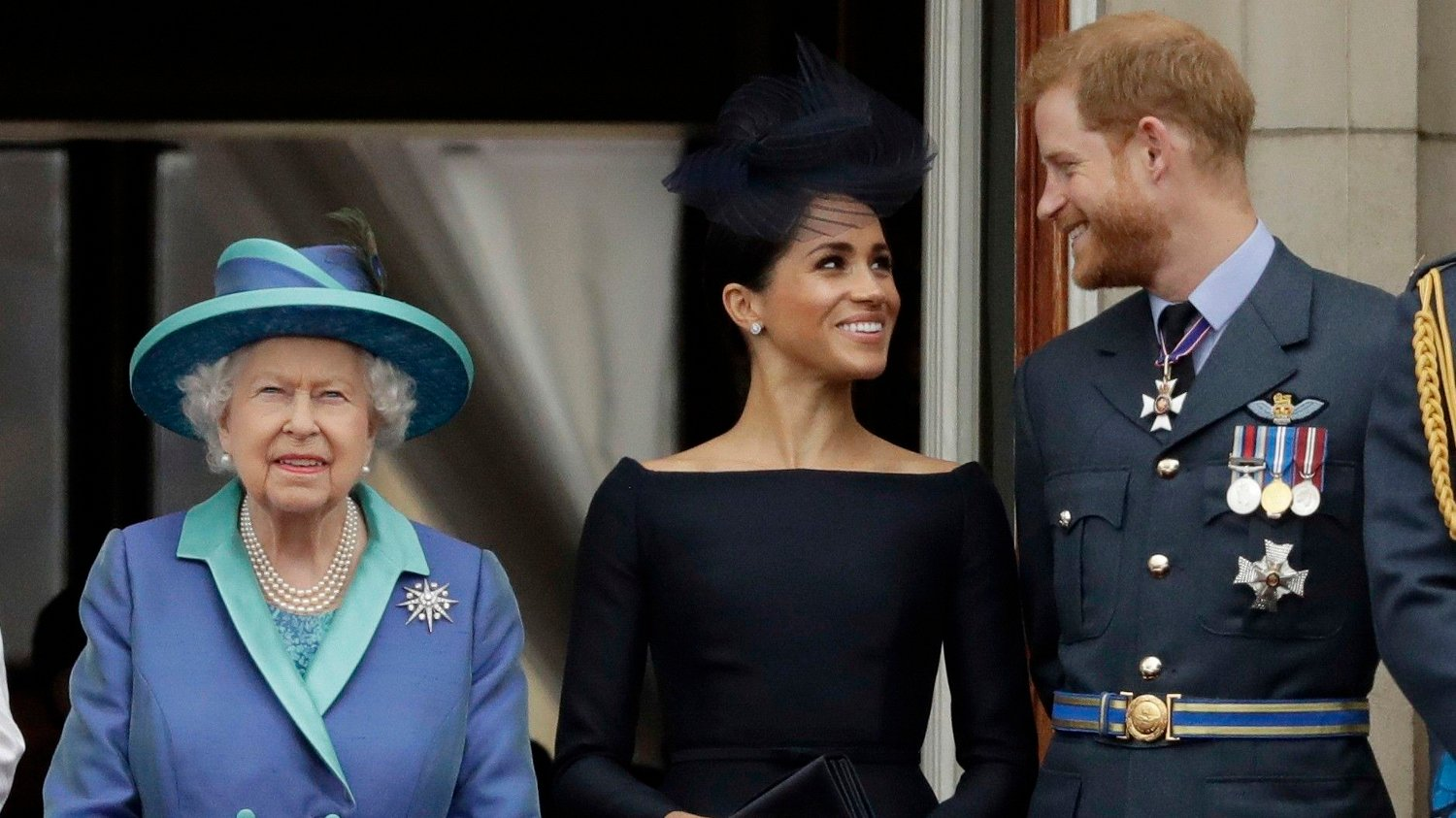 Britain Royal Rift FILE - In this Tuesday, July 10, 2018 file photo Britain's Queen Elizabeth II, and Meghan the Duchess of Sussex and Prince Harry watch a flypast of Royal Air Force aircraft pass over Buckingham Palace in London. As part of a surprise announcement distancing themselves from the British royal family, Prince Harry and his wife Meghan declared they will work to become financially independent _ a move that has not been clearly spelled out and could be fraught with obstacles.