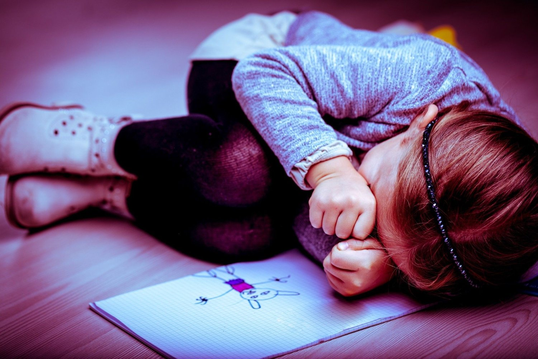 Barn ligger i fosterstilling på gulvet.