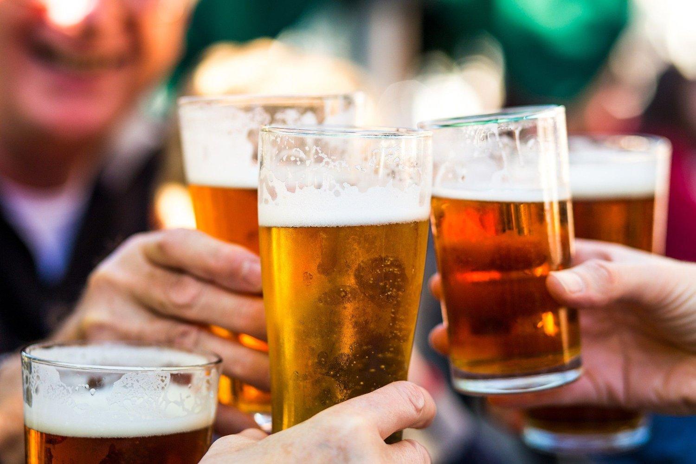 Mennesker skåler med fulle ølglass.