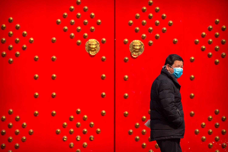 Mann med ansiktsmaske utenfor et stengt hotell i Beijing.