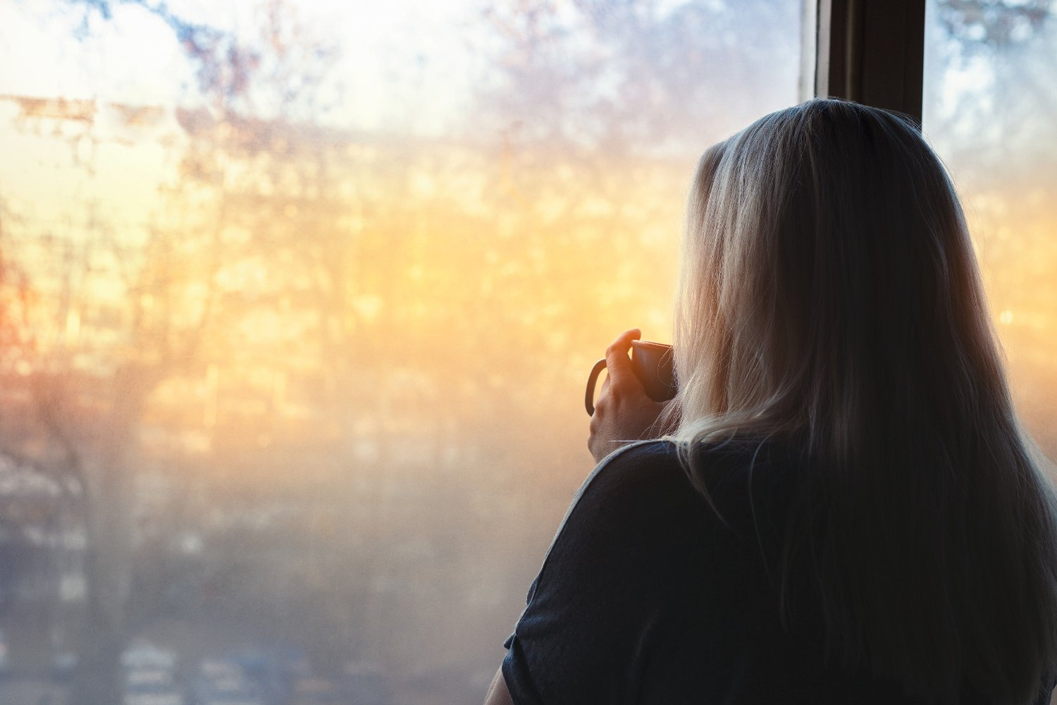 Blonde woman standing by the window, with coffee cup in hands, looking out into the morning light Blonde woman standing by the window, with coffee cup in hands, looking out into the morning light