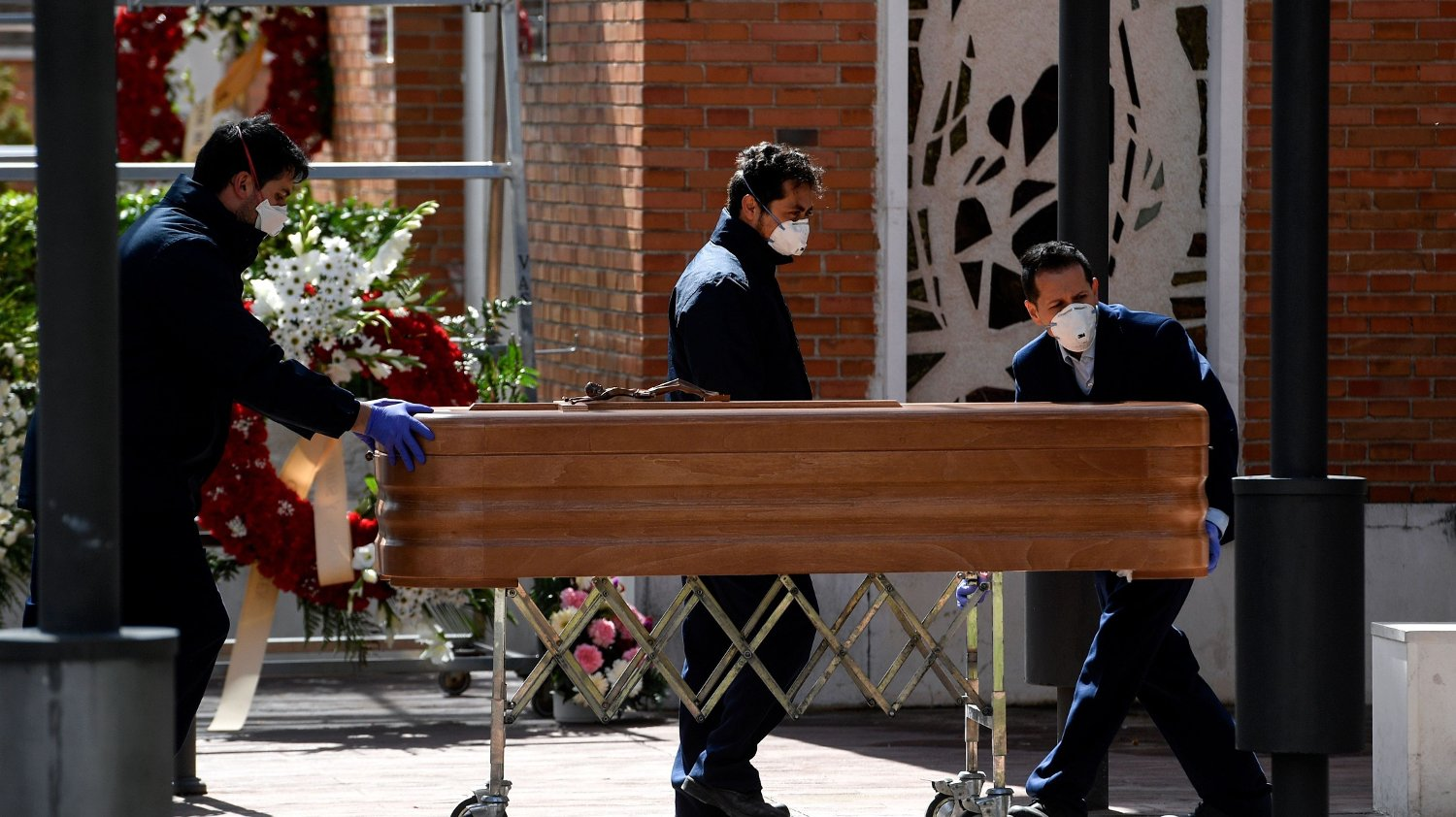 Mortuary employees wearing face masks wheel a coffin into the crematorium of La Almudena cemetery in Madrid on March 24, 2020 during the funeral of a COVID-19 coronavirus victim. - Spain has been one of the worst-hit countries, logging the third-highest number of deaths with the latest figures showing a toll of 2,696.