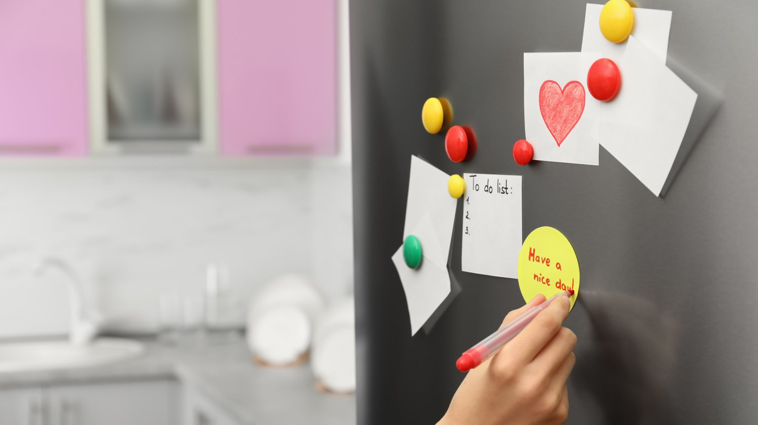 Woman writing message on note stuck to refrigerator door at home, closeup Woman writing message on note stuck to refrigerator door at home, closeup
