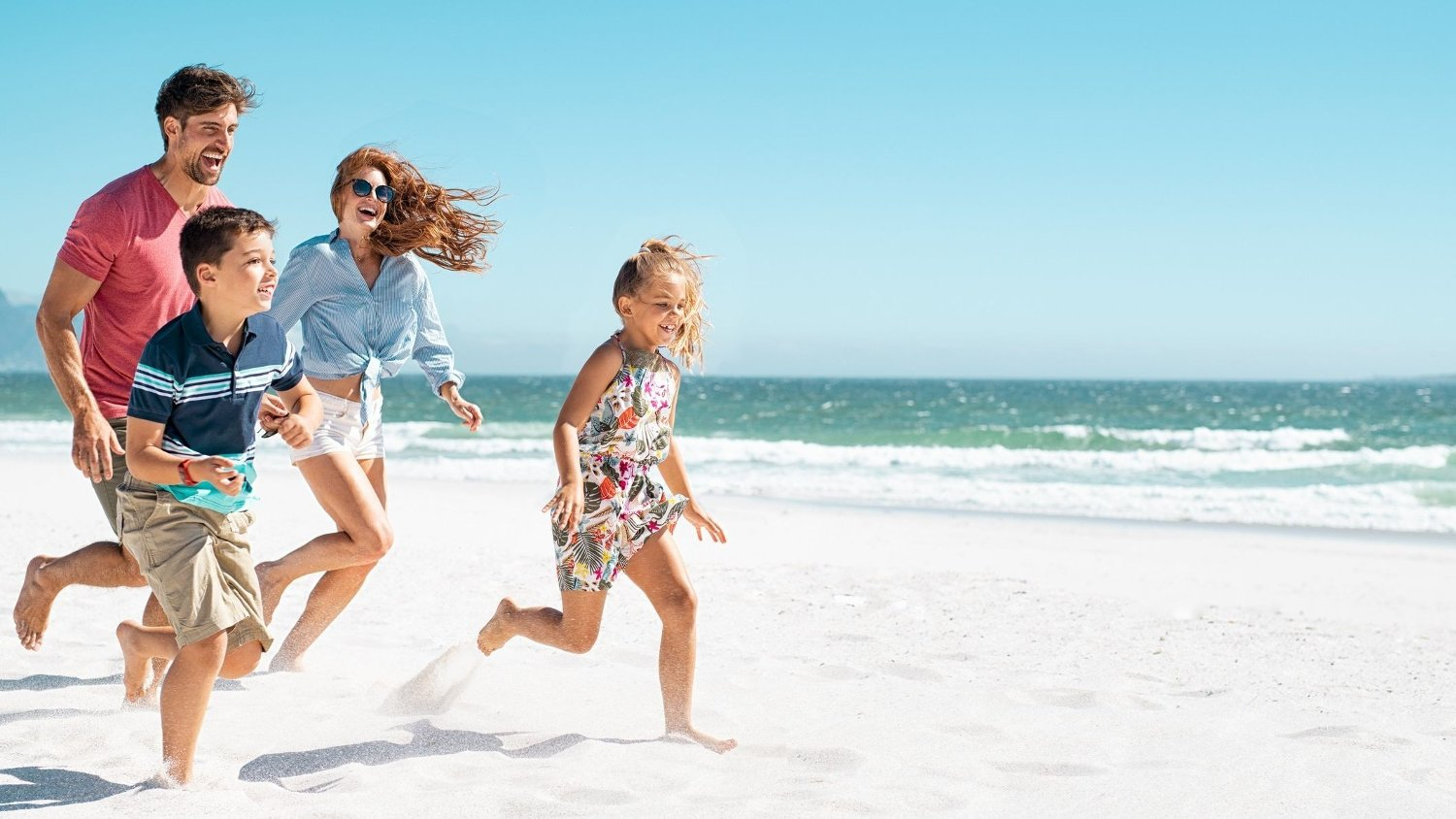 Happy family running on beach Cheerful young family running on the beach with copy space. Happy mother and smiling father with two children, son and daughter, having fun during summer holiday. Playful casual family enjoying playing at beach during vacaton.