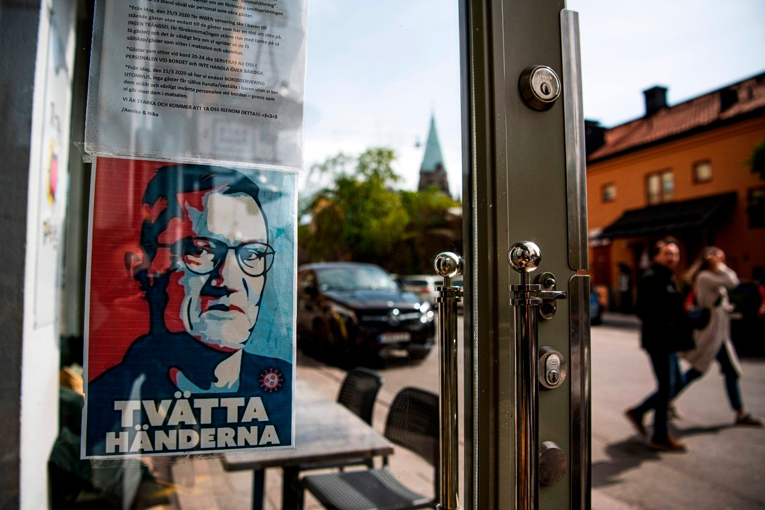 A sign with a portrait of Anders Tegnell, the face of the country's response to the novel coronavirus COVID-19 pandemic, is hanged at an entrance to a restaurant to instruct people to wash their hands on May 10, 2020 in Sodermalm, Stockholm.
