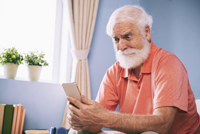 Shocking news Amazed senior man reading shocking message on his smartphone