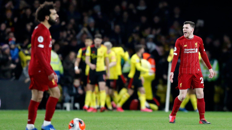 TITTELJAG: Liverpools ligagull vil bli overskygget av koronapandemien, mener Watfords Troy Deeney som i bakgrunn på dette bildet jubler etter å ha scoret mot Jürgen Klopps mannskap.