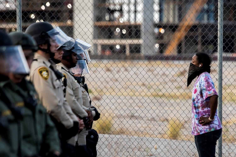 En enslig afroamerikansk kvinne står og ser på en «mur» av velutstyrte politimenn i Las Vegas.