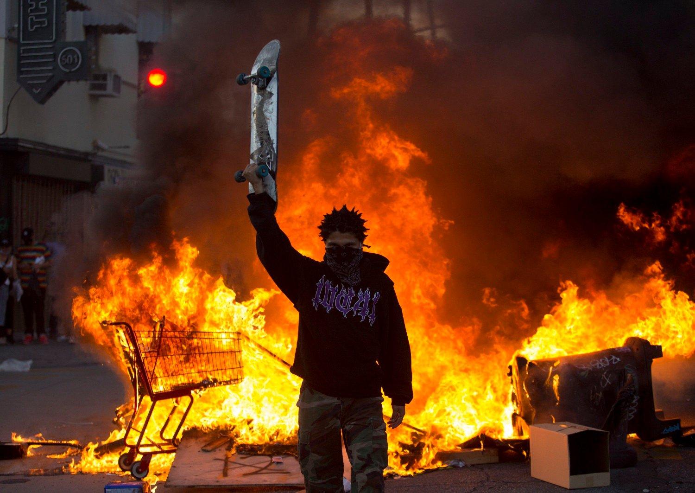 En demonstrant med et skateboard i hånden står foran et flammehav.