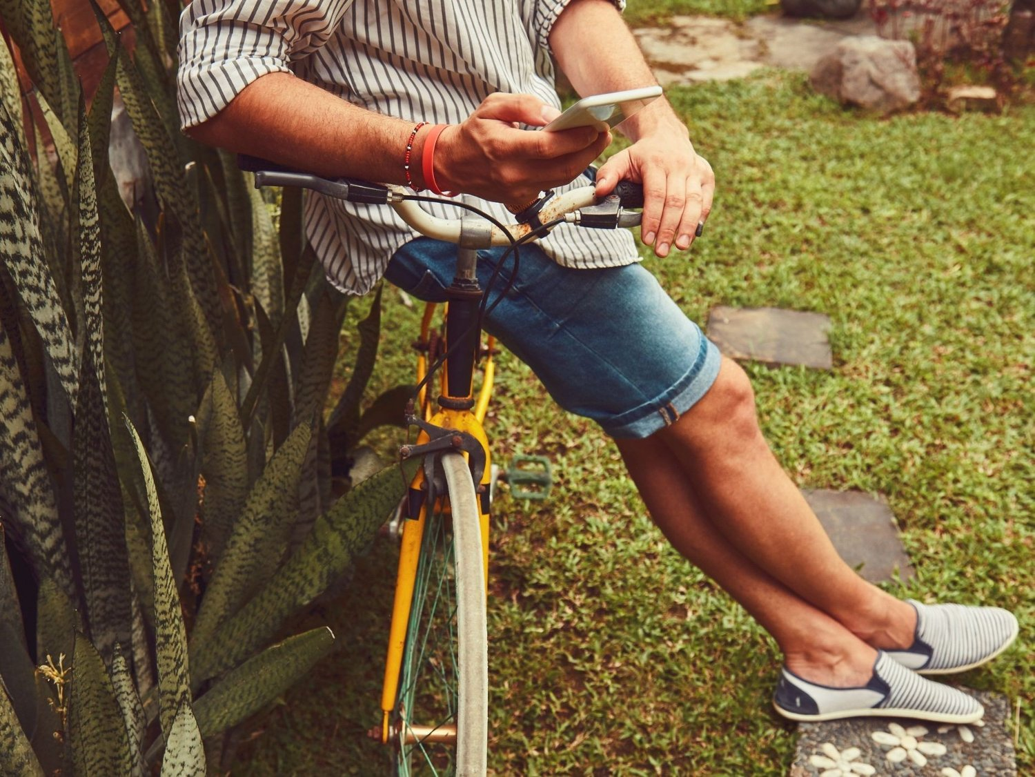 Modern man using cellphone while sitting on the grass with old bicycle. Modern man using cellphone while sitting on the grass with old bicycle.