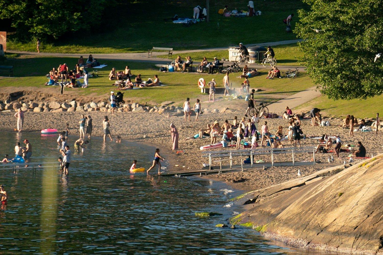 Svært mange nordmenn planlegger å tilbringe sommerferien i nærmiljøet. Bildet ble tatt søndag kveld, og viser folk som koser seg Hvervenbukta utenfor Oslo sentrum.