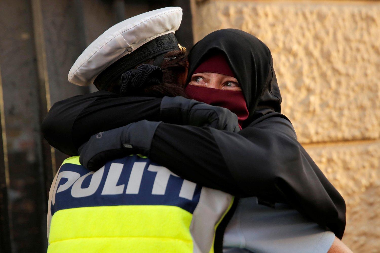 Ayah , som er iført nikab, feller en tåre mens hun omfavner en dansk politimann under en demonstrasjon 1. august mot det omstridte tildekkingsforbudet i Danmark.