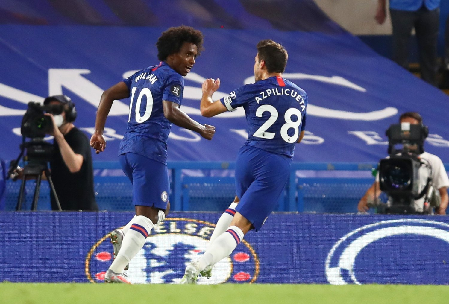 Soccer Football - Premier League - Chelsea v Manchester City - Stamford Bridge, London, Britain - June 25, 2020 Chelsea's Willian celebrates scoring their second goal with Cesar Azpilicueta, as play resumes behind closed doors following the outbreak of the coronavirus disease Julian Finney/Pool via REUTERS EDITORIAL USE ONLY. No use with unauthorized audio, video, data, fixture lists, club/league logos or