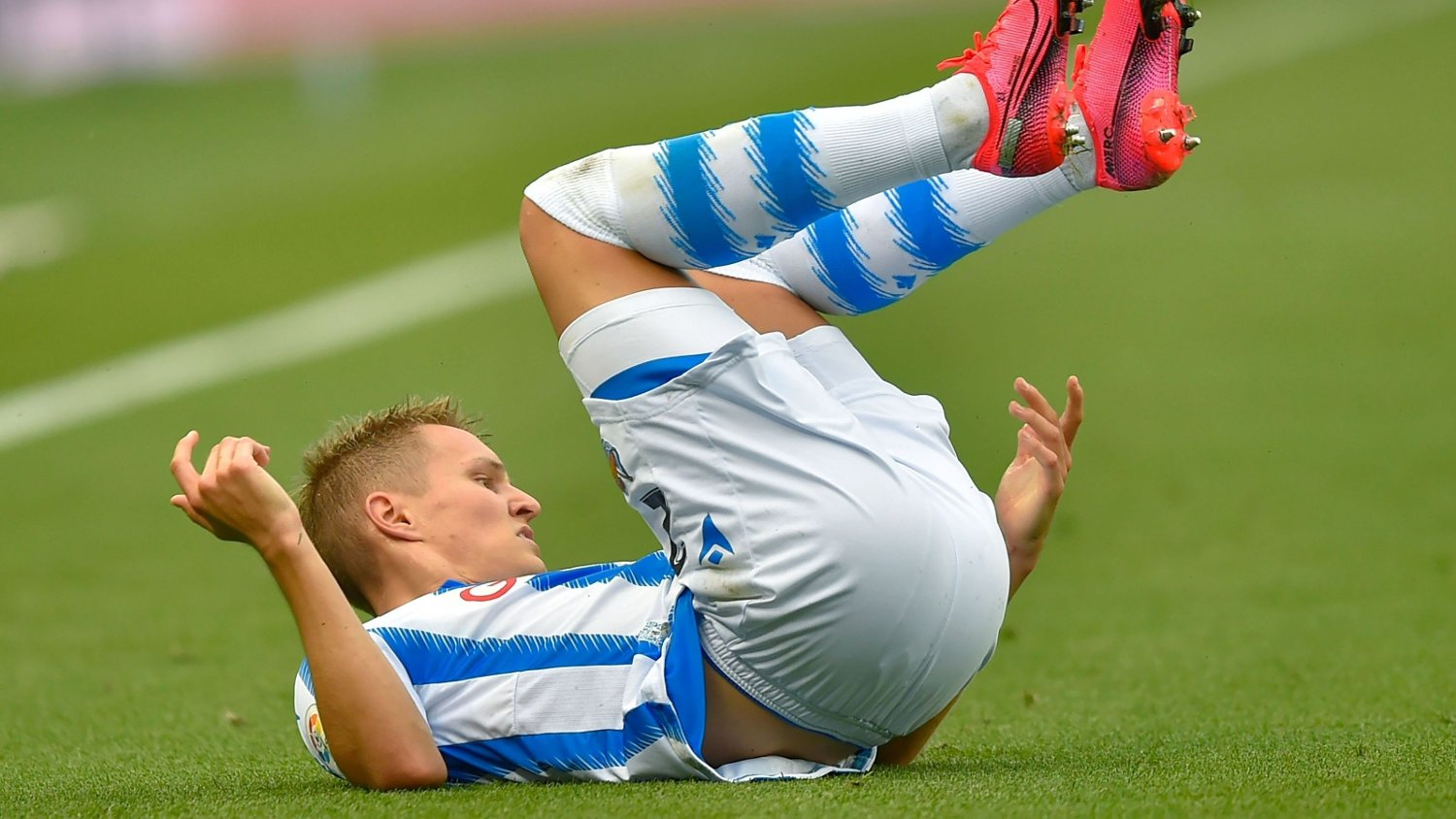 Real Sociedad's Norwegian midfielder Martin Odegaard falls during the Spanish league football match Real Sociedad against RC Celta de Vigo at the Reale Arena-Anoeta stadium in San Sebastian Stadium, on June 24, 2020.