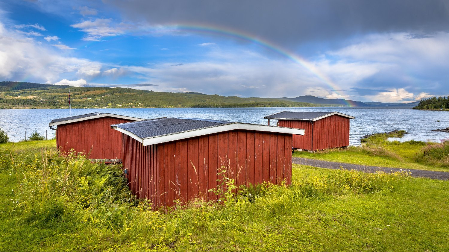 Idyllic red wooden cabins overseeing lake near Lillehammer, Norway. Under a rainbow