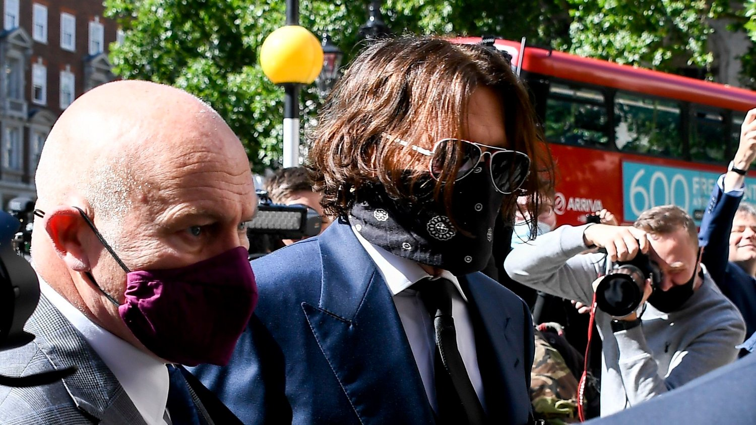 Britain Johnny Depp Johnny Depp, right, wearing a protective mask arrives at the Royal Court of Justice, in London, Tuesday, July 7, 2020. Johnny Depp is suing a tabloid newspaper for libel over an article that branded him a