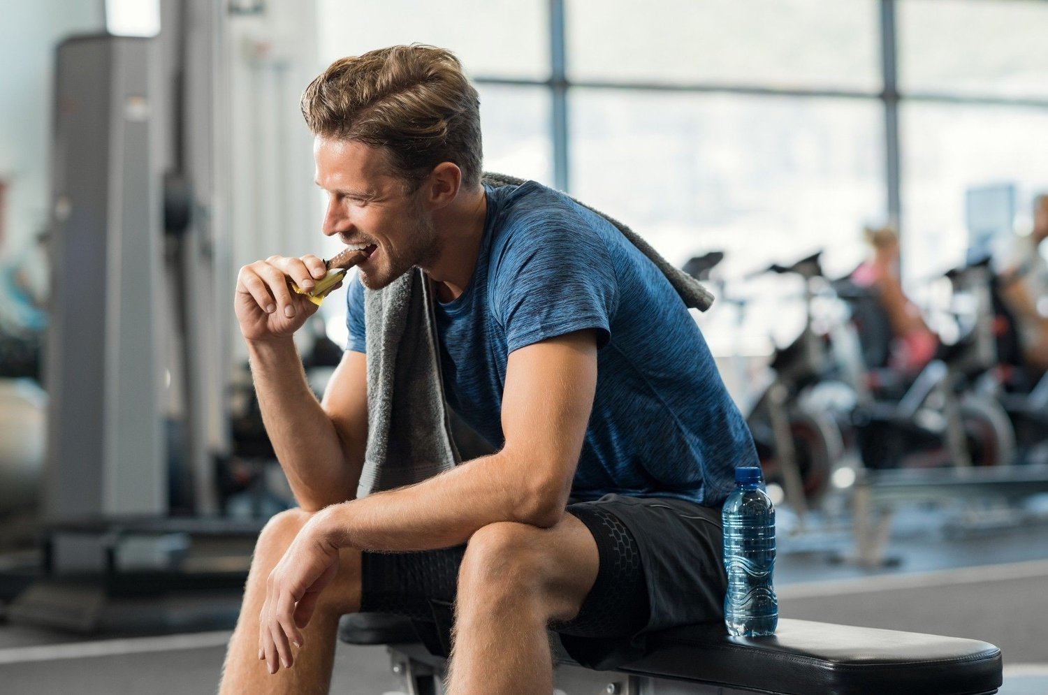 Man eating energy bar Sweaty young man eating energy bar at gym. Handsome mid guy enjoying chocolate after a heavy workout in fitness studio. Fit man biting a snack and resting on bench.