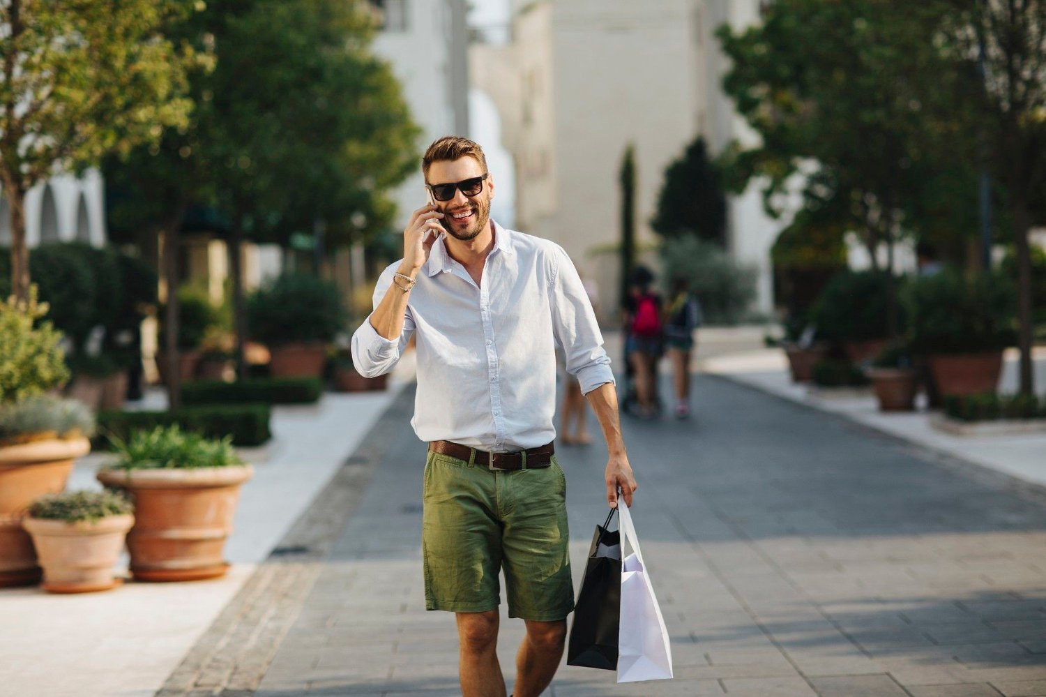 Young elegant man in the city Smiling elegant man walking on a city promenade at summer carrying shopping bags