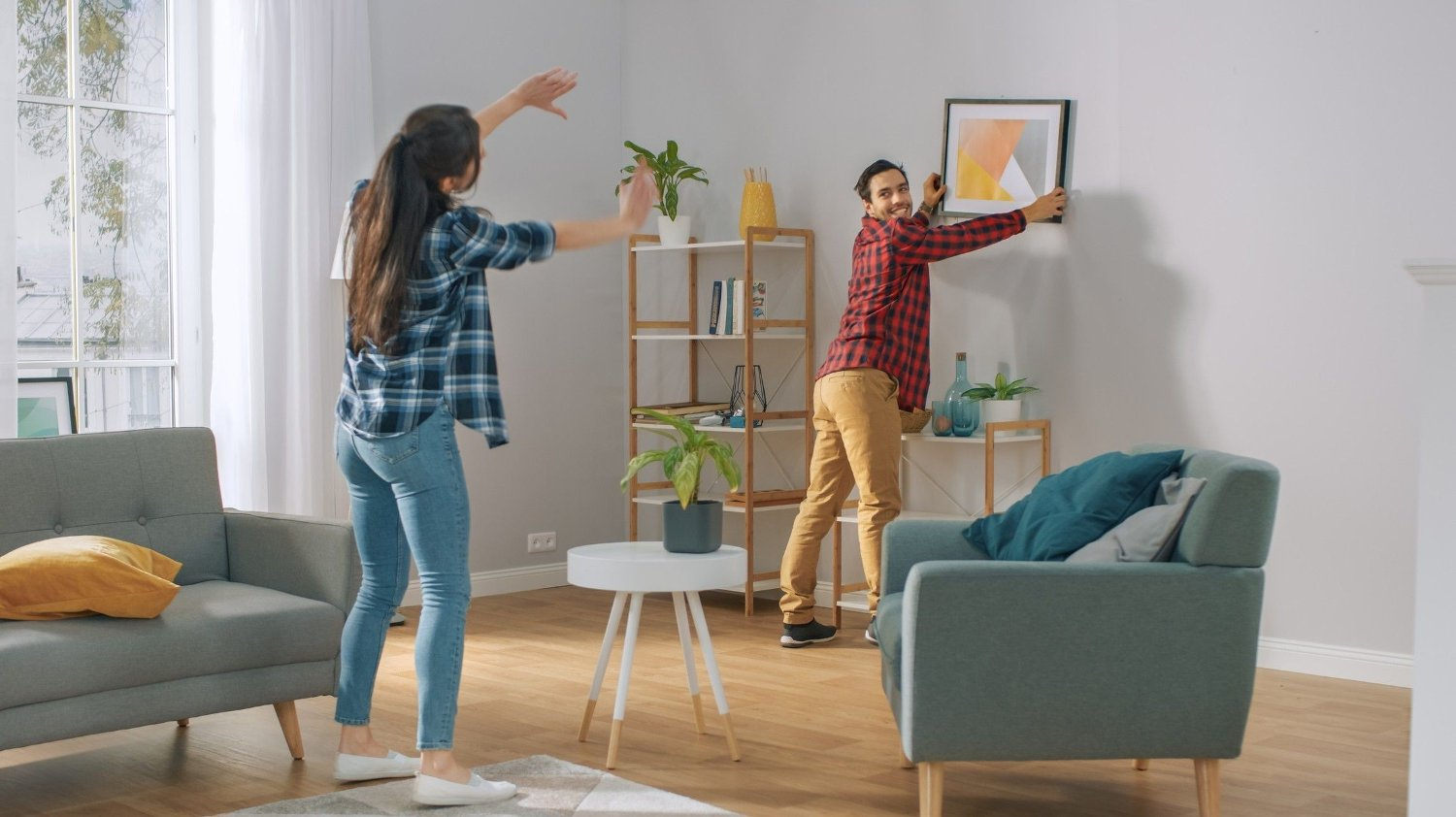 Happy Couple Hanging Picture on the Wall, Boyfriend Moves It, Girlfriend Tells Him when the Frame is Hanging Straight. Funny Moment in Young Couple's Life. Modern Stylish Apartment. Happy Couple Hanging Picture on the Wall, Boyfriend Moves It, Girlfriend Tells Him when the Frame is Hanging Straight. Funny Moment in Young Couple's Life. Modern Stylish Apartment.