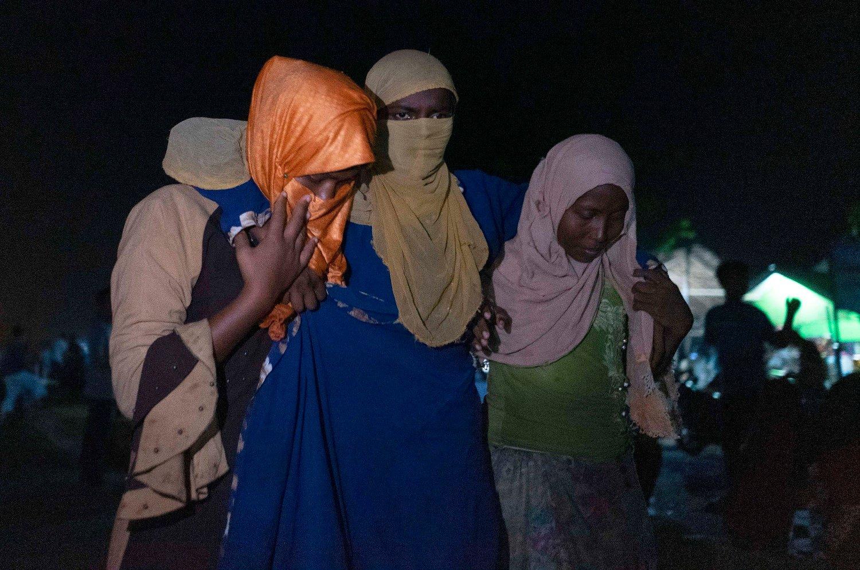 En rohingya-kvinne blir støttet av to andre. Indonesiske soldater, politi og Røde Halvmåne har bistått med å hjelpe de overlevende.