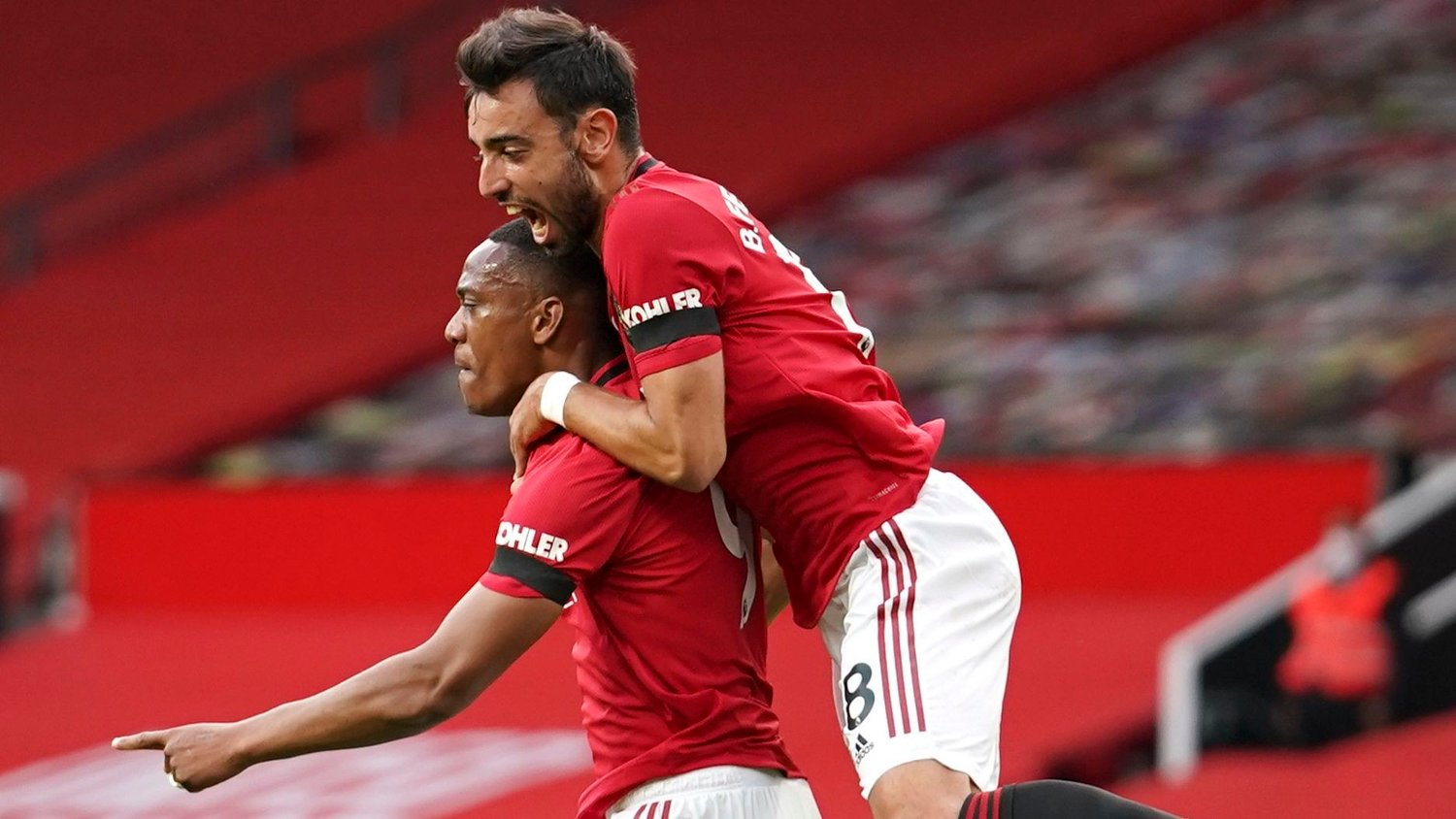 Manchester United's Anthony Martial, left, is congratulated by teammate Bruno Fernandes as he celebrates after scoring his ream's second goal during the English Premier League soccer match between Manchester United and Southampton at Old Trafford in Manchester, England, Monday, July 13, 2020.