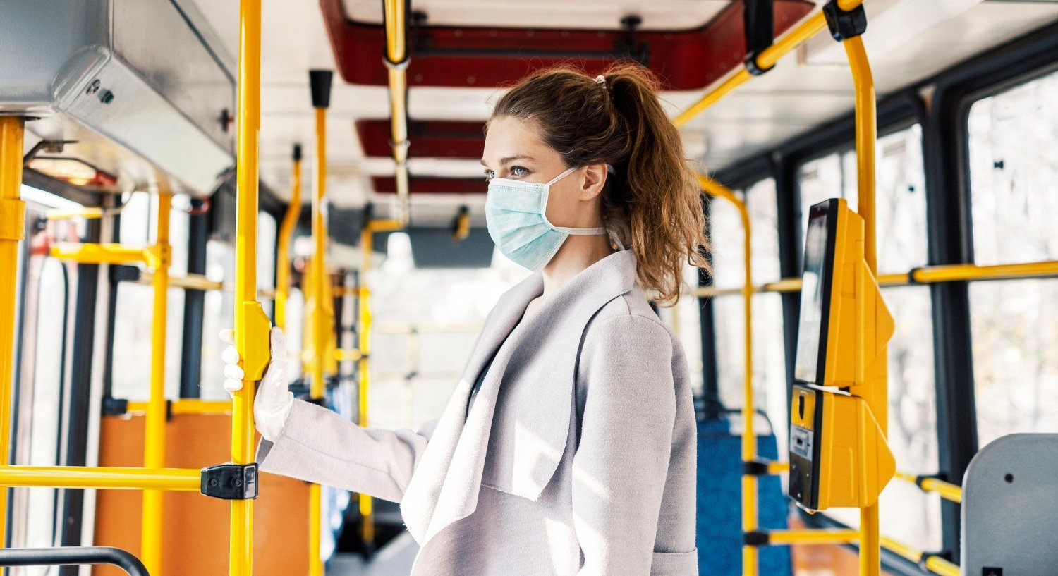 Virus protection in public transportation Woman wearing surgical protective mask going to work