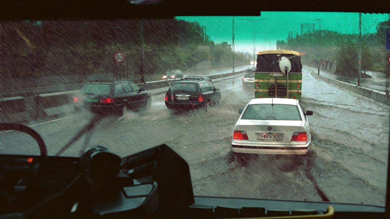 Illustrasjonsfoto: Regnvær og oversvømmelse på motorvei . Utsikt fra buss - fra førermiljø . Sjåfør.