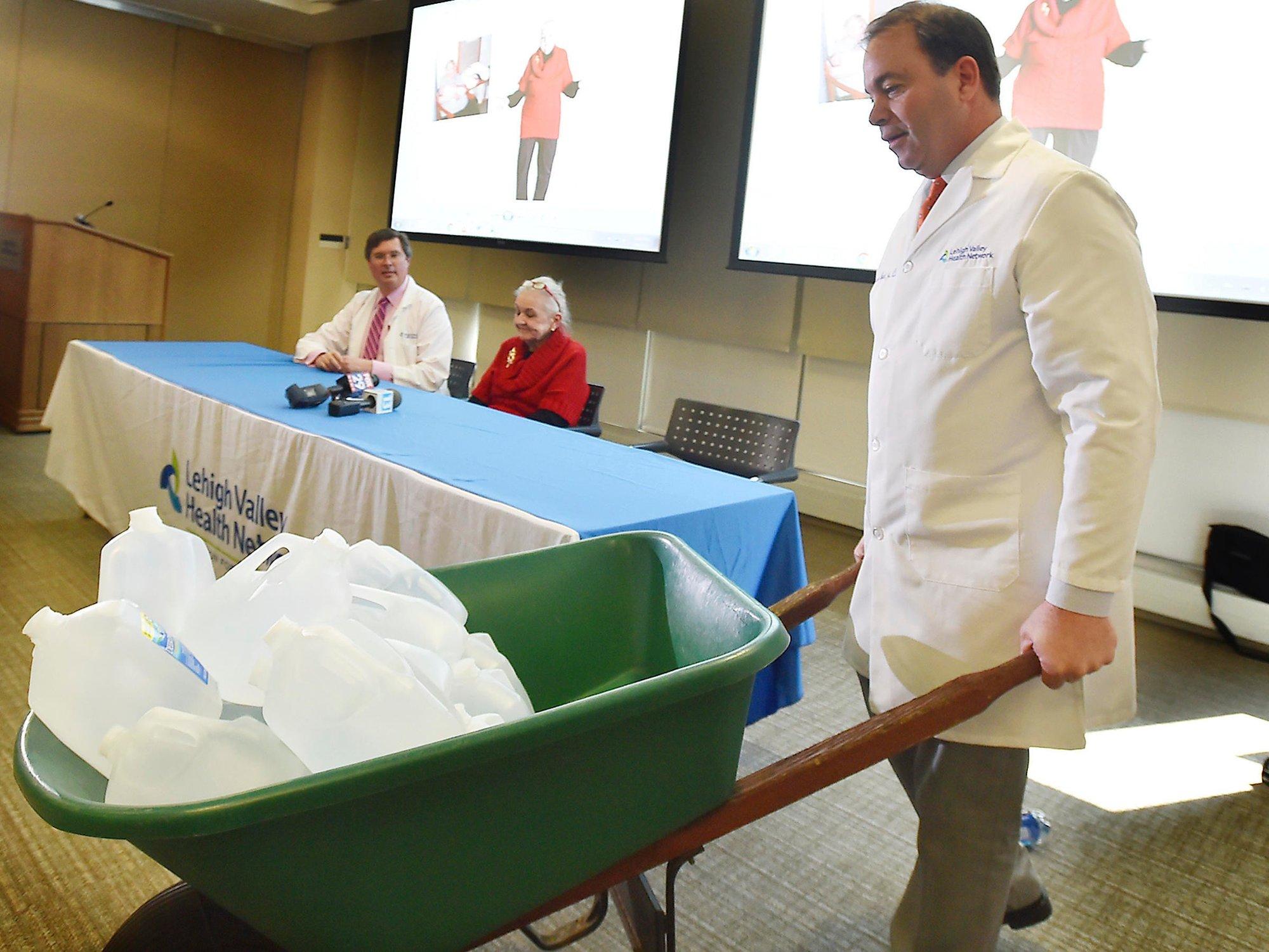 c2eea92c SÅ SVÆR: Doktor Randolph Wojcik Jr. viser fram vanntanker for å illustrere  volumet av svulsten som er operert ut Mary Clancey (71), som sitter i  bakgrunnen ...