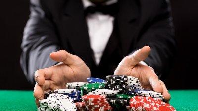Hender som holder rundt pokerbrikker