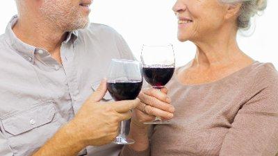 Eldre par drikker rødvin