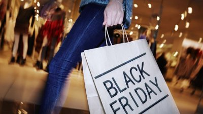 Visiting mall on Black Friday Modern shopper with Black Friday paperbag going in the mall
