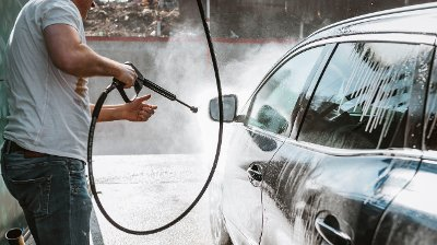 Man washing his car with high-pressure washing Man, wahsing his car in the stall of a car wash, using a high pressure water jet .Shot of a man washing his car under high pressure water outdoors.