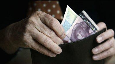 Sandvika 20040113. Eldre dame har tatt ut ut penger fra minibanken og står med lommeboken med penger i hendene, en tohundre og en etthundre seddel. Kanskje tenker hun på at pensjonskommisjonen la tirsdag fram sitt forslag til en fremtidig pensjonsordning som forhåpentligvis vil begynne å virke fra 2010. Pensjonister. Økonomi. Privatøkonomi. Lommebok. Pensjonist. Alderdom.