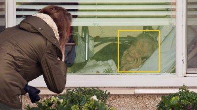 På bildet kan du se Lori Spencer som snakker på telefonen gjennom et vindu med moren, Judie Shape , som nå blir testet for coronaviruset. Judie Shape er beboer ved Life Care Center of Kirkland.