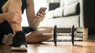 Man using smartphone during workout at home. Online personal trainer or on mobile phone. Internet fitness class or video course. Taking a break. Lazy guy with cellphone while training.