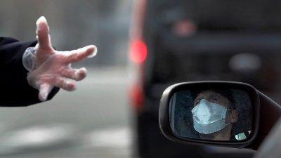 En politimann i Paris henvender seg til en bilist som er iført munnbind tirsdag. Politimannen er iført plasthansker for å beskytte seg mot koronaviruset.