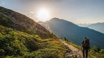Venetberg, Austria - August 02 2017: Single hiker in the early morning at sunrise on a trekking path in the Lechtaler Alps Venetberg, Austria - August 02 2017: Single hiker in the early morning at sunrise on a trekking path in the Lechtaler Alps